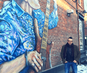 Rich Fracasse stands in front of a work of street art by Will Teran created to adorn Teran's friend's building, Fracasse's 101 Liberty Street.
