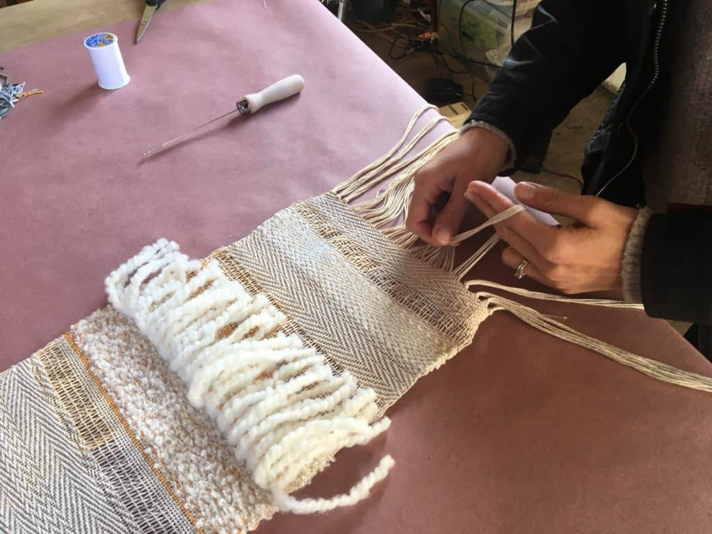 Tying off the end of a loom scarf in Newburgh weaving workshop