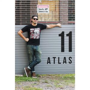 Pat Nunnari poses in front of Atlas Studios' 11 Spring Street sign which he designed and crafted.
